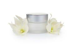 Kosmetische roomkruik en bloemen Stock Foto