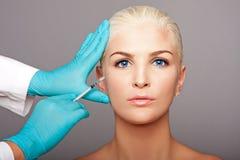Kosmetischer plastischer Chirurg, der Ästhetikgesicht einspritzt Stockfotos
