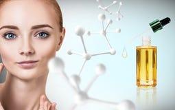Kosmetisches Öl auf Frau ` s Gesicht nahe weißem Molekül Stockfotos
