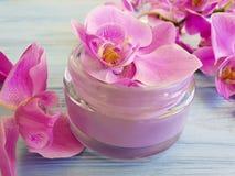 Kosmetisches Orchideenblumengesundheitshygiene-Behältersahneprodukt auf einem blauen hölzernen Hintergrund stockbild