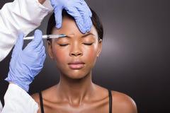 Kosmetisk doktor som injicerar pannan Fotografering för Bildbyråer
