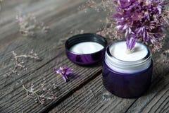 Kosmetisk flaska och Violet Flower för framsidakräm royaltyfri bild