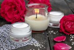 Kosmetisk kräm och rosor med kronblad och en brinnande stearinljus på den gamla träbakgrunden royaltyfri bild