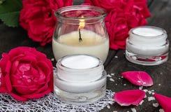 Kosmetisk kräm och rosor med kronblad och en brinnande stearinljus på den gamla träbakgrunden royaltyfria foton