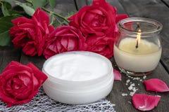 Kosmetisk kräm och rosor med kronblad och en brinnande stearinljus på den gamla träbakgrunden fotografering för bildbyråer
