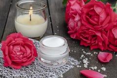 Kosmetisk kräm och rosor med kronblad och en brinnande stearinljus på den gamla träbakgrunden arkivfoton