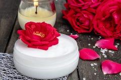 Kosmetisk kräm och rosor med kronblad och en brinnande stearinljus på den gamla träbakgrunden arkivbilder
