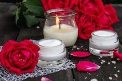 Kosmetisk kräm och rosor med kronblad och en brinnande stearinljus på den gamla träbakgrunden royaltyfria bilder