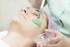 Kosmetisk maskering för process av massagen och ansiktsbehandlingar royaltyfri bild