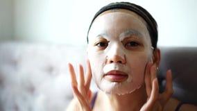 Kosmetisk maskering på framsidabehandlingkvinnor arkivfilmer