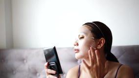 Kosmetisk maskering på framsidabehandlingkvinnor stock video