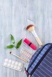 Kosmetisk påse med preventivmedel och preventivpillerar på träcopyspace för bästa sikt för tabellbakgrund Arkivfoto