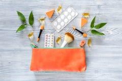 Kosmetisk påse med preventivmedel och preventivpillerar på träcopyspace för bästa sikt för tabellbakgrund Fotografering för Bildbyråer