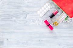 Kosmetisk påse med preventivmedel och preventivpillerar på träcopyspace för bästa sikt för tabellbakgrund Royaltyfri Fotografi