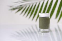 Kosmetisk produkt i en krus och ett bambublad p? ljus bakgrund som annonserar begrepp arkivfoto