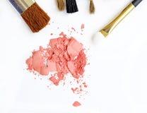 Kosmetisk pulverborste och krossad rodnadpalett som isoleras på vit Arkivbild
