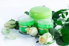 Kosmetisk sammansättning av krämflaskor och rosor Arkivfoton