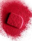 Kosmetisk svamp som dammas av med röd ögonskugga bakgrund isolerad white royaltyfri foto