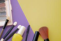 kosmetisk tillbehör Borste för rodnad, borste, fernissa på en guling, purpurfärgad bakgrund arkivfoton