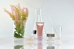 Kosmetiska flaskbehållare med gröna växt- sidor och vetenskaplig glasföremål, tom etikettpacke för att brännmärka modellen Royaltyfri Bild