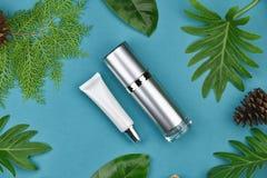 Kosmetiska flaskbehållare på grön växt- sidabakgrund, tom etikett för att brännmärka modellen Royaltyfria Bilder