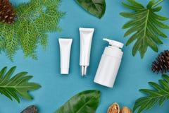 Kosmetiska flaskbehållare på grön växt- sidabakgrund, tom etikett för att brännmärka modellen Fotografering för Bildbyråer