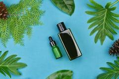Kosmetiska flaskbehållare på grön växt- sidabakgrund, tom etikett för att brännmärka modellen Arkivfoto