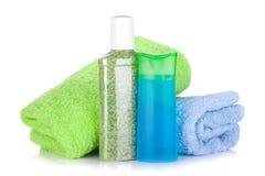 Kosmetiska flaskor med handdukar Fotografering för Bildbyråer