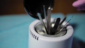 Kosmetiska metallhjälpmedel desinficeras i steriliseringsapparaten för den glass pärlan stock video