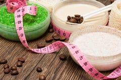 Kosmetiska produkter för anti-cellulite med kroppen som mäter bandet royaltyfri foto