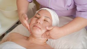 kosmetiskt tillvägagångssätt Närbildframsida av en asiatisk kvinna Cosmetologisten applicerar krämen till den kvinnliga halsen oc stock video