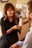 Kosmetolog Advising Male Client på skönhetsprodukter Royaltyfria Bilder