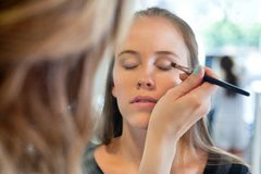Kosmetolog Applying Eye Make upp Arkivfoto