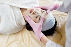 Kosmetolog Applying Sheet Mask arkivfoton