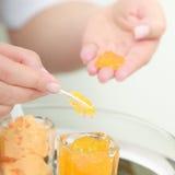 Kosmetolog med orange fuktakräm. Skincare. Skönhetsalong. Fotografering för Bildbyråer