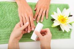 Kosmetolog Polishing The Nails Royaltyfri Bild