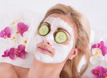 Kosmetolog som applicerar den ansikts- maskeringen på framsida av kvinnan royaltyfri bild