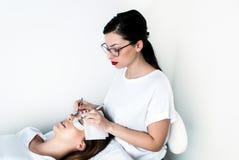 Kosmetolog som arbetar på förbättring av siden- ögonfrans i en skönhetstudio Royaltyfri Bild