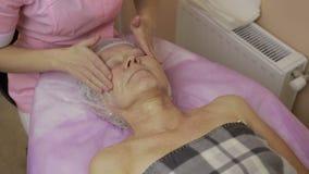 Kosmetolog som fuktar framsidan för kvinna` s med kräm arkivfilmer