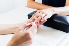 Kosmetolog som gör en manikyr i salong Fotografering för Bildbyråer