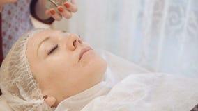 Kosmetolog som gör hudbehandling med den ultraljuds- maskinen lager videofilmer