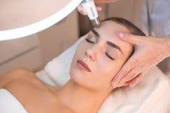 Kosmetolog som genomgår anti--åldras föryngringtillvägagångssätt på kvinnaframsida Royaltyfri Bild
