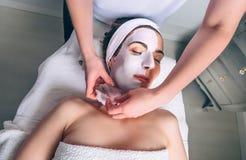 Kosmetolog som tar bort den ansikts- maskeringen till kvinnan i brunnsort Arkivbild
