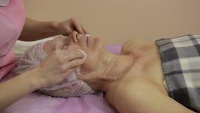 Kosmetolog som tar bort kräm från framsida för kvinna` s lager videofilmer