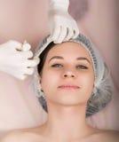 Kosmetolog som undersöker framsidan av en ung kvinnlig klient på brunnsortsalongen kosmetologen tar bort patientens framsidamaske Arkivfoto