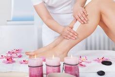 Kosmetolog som vaxar kvinnas ben Arkivbild