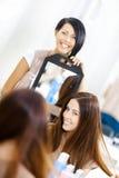 Kosmetolog som visar frisyren av klienten i spegel royaltyfria foton