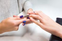 Kosmetologbrämnagelband av den kvinnliga klienten Royaltyfri Fotografi