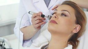 Kosmetologen använder iontophoresisrullen för framsida för klient` s fotografering för bildbyråer