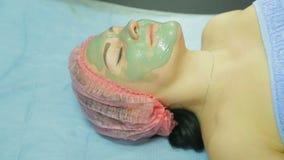 Kosmetologen applicerar en kosmetisk maskering av grå lera med en borste på framsidan av en kvinna lager videofilmer